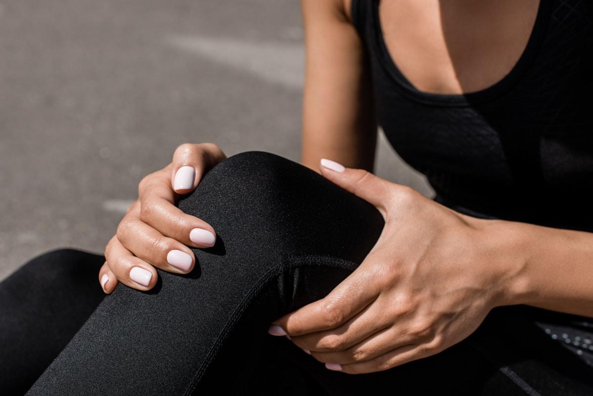 Sportlerin hält sich das Knie