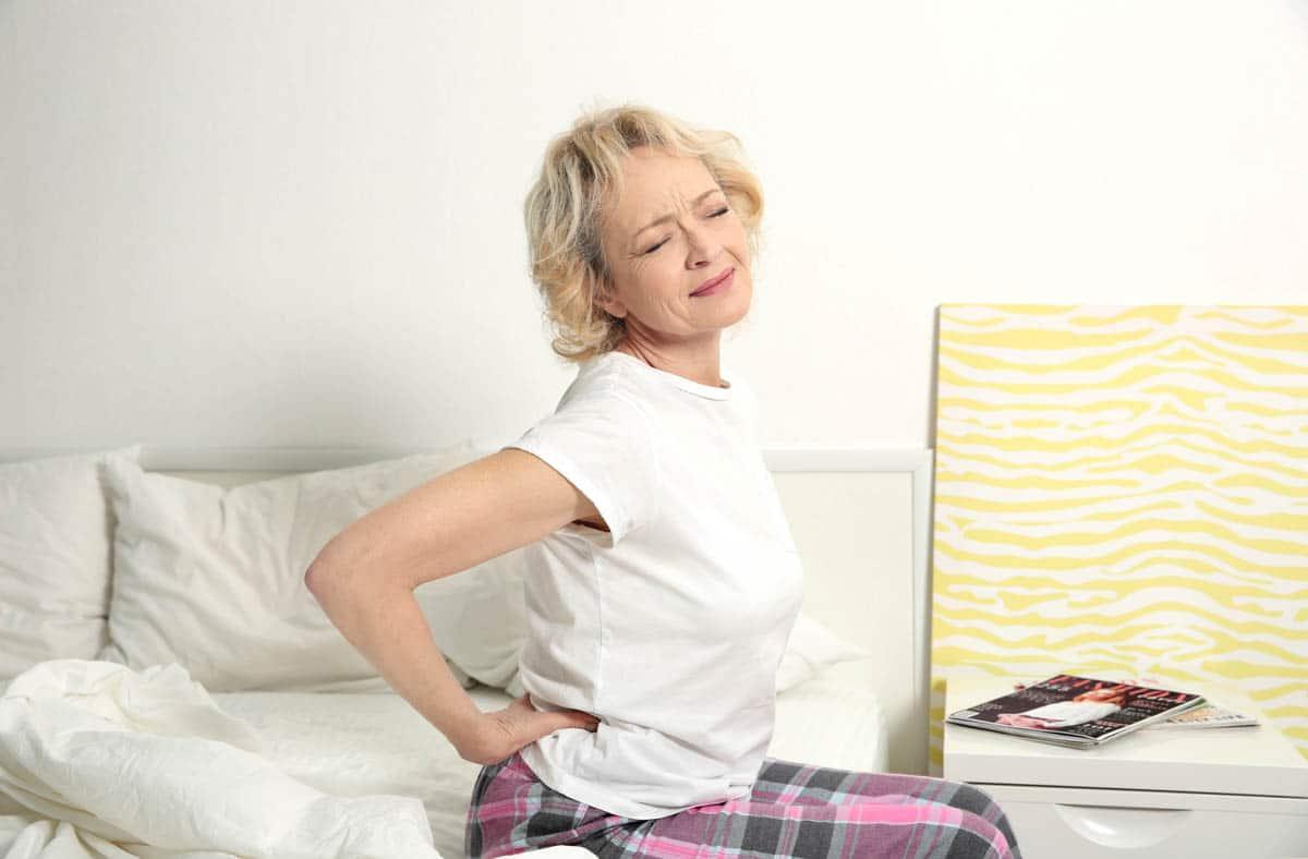 Frau fasst sich an die Hüfte - Coxarthrose?