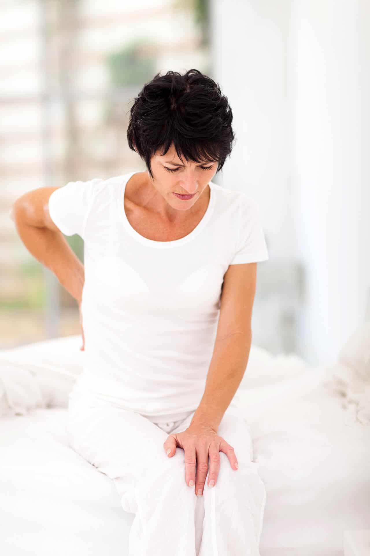 Frau mit Schmerzen im unteren Rückenbereich