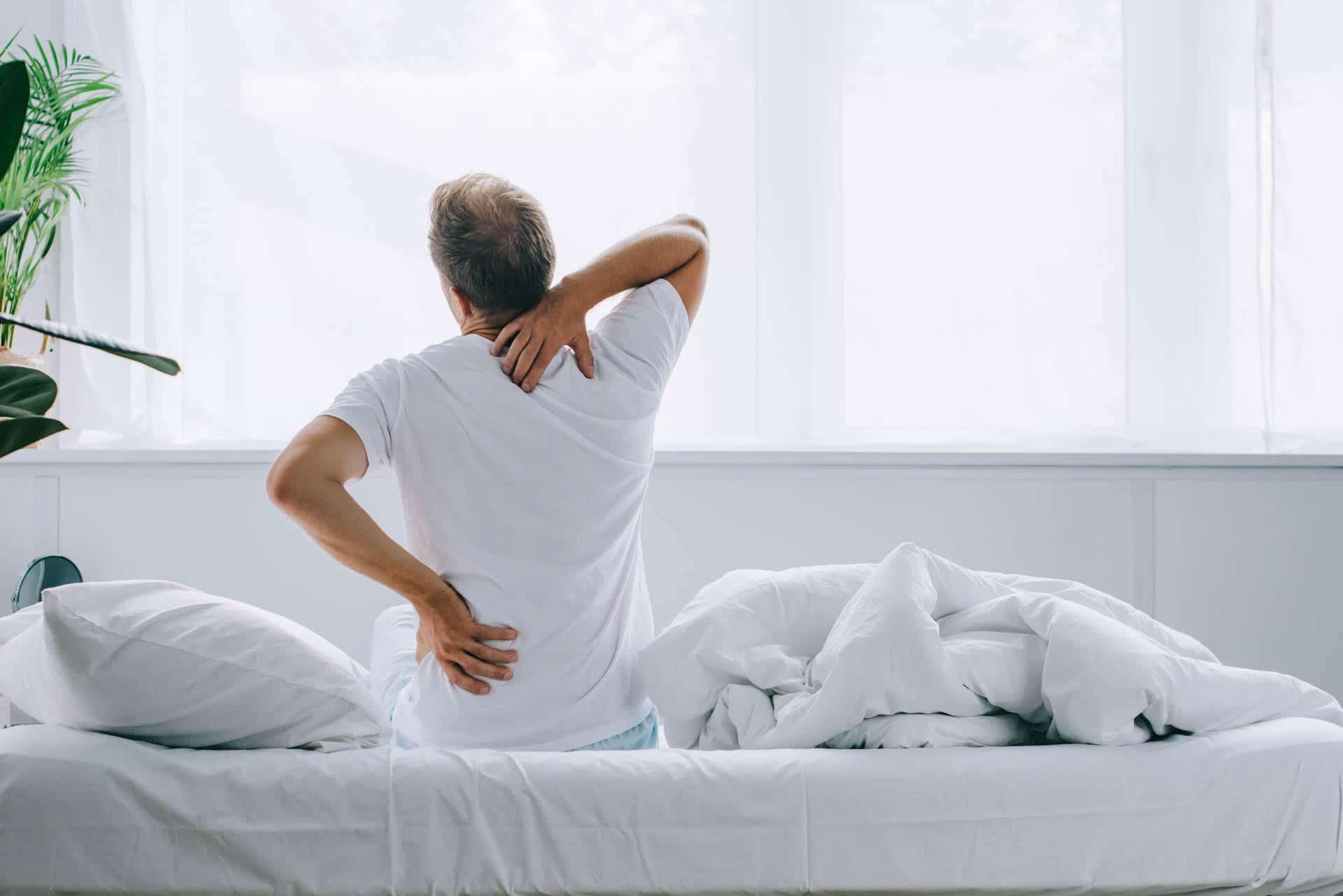 Mann im Bett mit Schmerzen im unteren Rücken